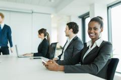 Молодые бизнесмены сидя на столе переговоров и уча Стоковое фото RF