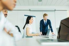Молодые бизнесмены сидя на столе переговоров и уча Стоковое Изображение