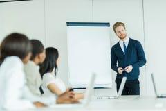 Молодые бизнесмены сидя на столе переговоров и уча Стоковые Изображения