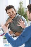 Молодые бизнесмены сидя на таблице и обсуждая новый проект Стоковая Фотография