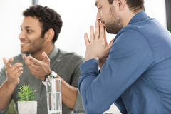 Молодые бизнесмены сидя на таблице и обсуждая новый проект Стоковые Фотографии RF