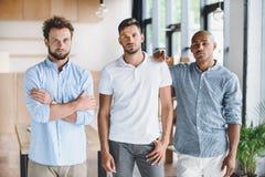 Молодые бизнесмены смотря камеру пока стоящ в офисе Стоковые Фото