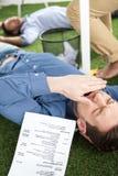 Молодые бизнесмены спать на ковре зеленой травы на современном офисе Стоковые Изображения RF