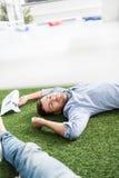 Молодые бизнесмены спать на ковре зеленой травы на современном офисе Стоковое фото RF