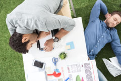 Молодые бизнесмены спать на ковре таблицы и зеленой травы на современном офисе Стоковая Фотография