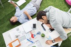 Молодые бизнесмены спать на ковре таблицы и зеленой травы на современном офисе Стоковая Фотография RF