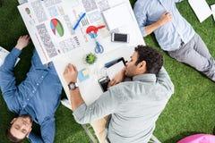 Молодые бизнесмены спать на ковре таблицы и зеленой травы на современном офисе Стоковое Изображение