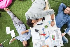 Молодые бизнесмены спать на ковре таблицы и зеленой травы на современном офисе Стоковое Фото