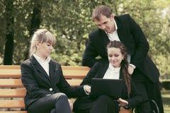 Молодые бизнесмены с компьтер-книжкой в парке города Стоковые Изображения RF