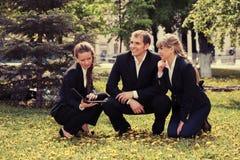 Молодые бизнесмены с компьтер-книжкой в парке города Стоковые Изображения
