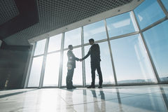 Молодые бизнесмены трясут руки друг с другом стоя против панорамных окон Стоковые Фото
