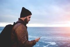 Молодые бородатые данные по чтения человека на телефоне клетки во время отключения стоковые фотографии rf
