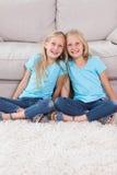 Молодые близнецы сидя на ковре Стоковое Изображение