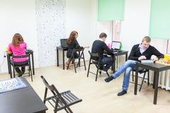 Молодые взрослые занимаясь серфингом интернет в со-работая комнате Стоковое Изображение