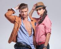 Молодые вскользь пары представляя на предпосылке студии стоковые фотографии rf