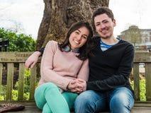 Молодые гетеросексуальные пары сидя на скамейке в парке Стоковые Фотографии RF