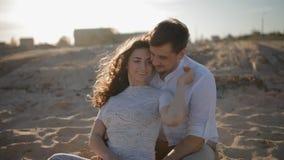 Молодые европейские пары сидят на песке акции видеоматериалы