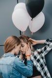 Молодые лесбосские пары держа воздушные шары и обнимая outdoors Стоковая Фотография