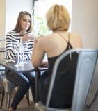 Молодые женские друзья имея кофе на кафе Стоковое Изображение