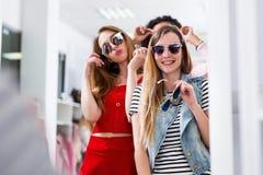 Молодые женские друзья пробуя на солнечных очках смеясь над и имея потехой в вспомогательном магазине стоковые изображения
