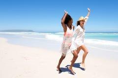 Молодые женские друзья смеясь над и играя на пляже Стоковые Фото