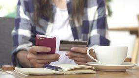 Молодые женские руки покупая товары от интернета на smartphone с кредитной карточкой Стоковая Фотография