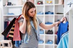 Молодые женские shopaholic держа хозяйственные сумки и дамы выбирать носят в магазине одежды Стоковые Изображения