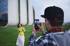 Молодые женщина и человек пар делают фото на мобильном телефоне в Баку Современные человек и женщина битника используя мобильный  Стоковая Фотография RF