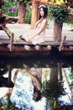 Молодые женщины Азии сидя в красочном цветочном саде Стоковые Фотографии RF