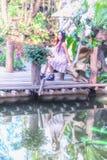 Молодые женщины Азии сидя в красочном цветочном саде Стоковые Изображения