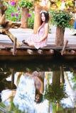Молодые женщины Азии сидя в красочном цветочном саде Стоковая Фотография RF