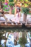 Молодые женщины Азии сидя в красочном цветочном саде Стоковое Изображение