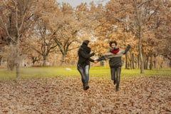Молодые женщины бежать в парке над полем вполне листьев Aut Стоковое Изображение