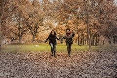 Молодые женщины бежать в парке над полем вполне листьев Aut Стоковое Изображение RF