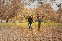 Молодые женщины бежать в парке над полем вполне листьев Aut Стоковое фото RF