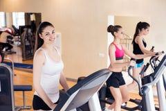 Молодые женщины бежать на третбане в спортзале Стоковые Фото