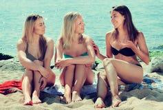 Молодые женщины беседуя на пляже Стоковое Изображение RF