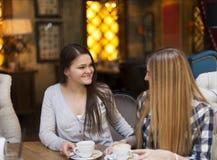 Молодые женщины выпивая кофе в кафе Стоковое Фото