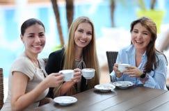 Молодые женщины выпивая кофе в кафе outdoors Стоковая Фотография