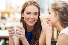 Молодые женщины выпивая кофе и говоря на кафе Стоковые Фото