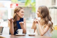 Молодые женщины выпивая кофе и говоря на кафе Стоковое Изображение