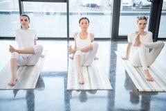 Молодые женщины выполняя йогу располагают совместно на циновки йоги Стоковые Изображения