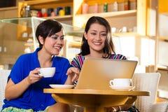 Молодые женщины в азиатском coffeeshop Стоковые Изображения
