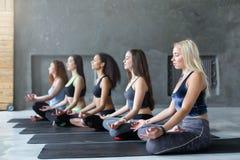 Молодые женщины в занятиях йогой, ослабляют представление раздумья Стоковая Фотография