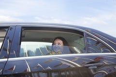 Молодые женщины в заднем сиденье автомобиля смотря из окна. Стоковое Фото