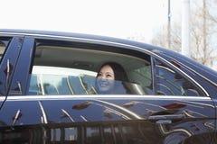 Молодые женщины в заднем сиденье автомобиля смотря из окна. Стоковое Изображение