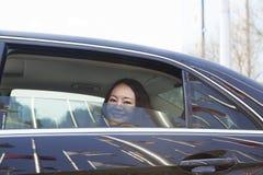 Молодые женщины в заднем сиденье автомобиля смотря из окна. Стоковое Изображение RF
