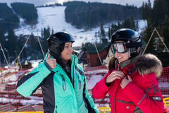 Молодые женщины в костюмах лыжи, с шлемами и стоять изумлённых взглядов лыжи Стоковое Фото