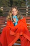 Молодые женщины в одеяле дуют в ее горячем coffe на зябком wint Стоковая Фотография RF