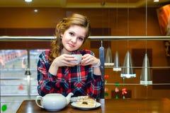 Молодые женщины в чае рубашки шотландки выпивая в кафе Стоковая Фотография